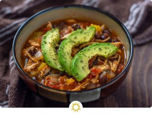 Chicken tortilla soup topped with sliced avocado and parsley in a brown bowl with a brown towel behind on a wooden surface (with logo overlay)