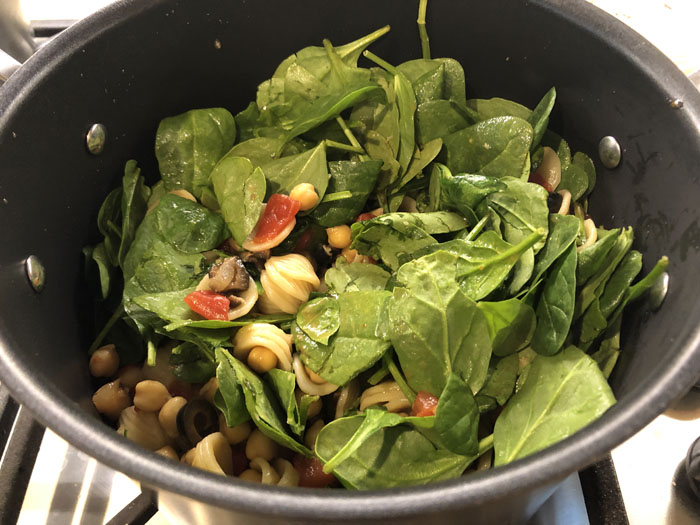 Large stockpot with pasta noodles, chickpeas, and spinach leaves over a gas stovetop