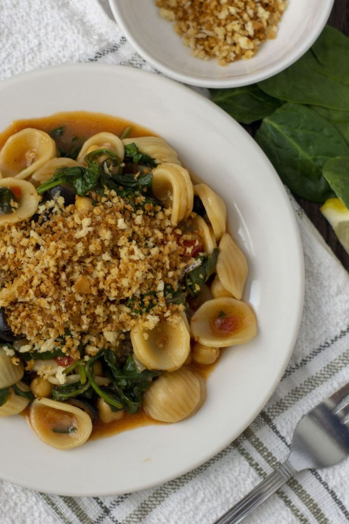 Chickpea and Spinach Orecchiette on a white plate on top of a white and green towel with a fork on it next to a small white bowl of toasted breadcrumbs and spinach and lemon slices (vertial)