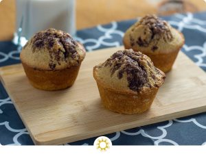 3 Cinnamon Swirl Muffins with Streusel Topping on a bamboo board on top of a grey and white placemat with a glass of milk behind all on a wooden surface (with logo overlay)