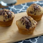 3 Cinnamon Swirl Muffins with Streusel Topping on a bamboo board on top of a grey and white placemat with a glass of milk behind all on a wooden surface (with title overlay)