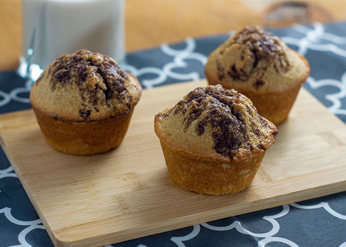 3 Cinnamon Swirl Muffins with Streusel Topping on a bamboo board on top of a grey and white placemat with a glass of milk behind all on a wooden surface
