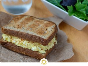 Egg Salad Sandwich on a brown piece of paper with a glass of water and white bowl of salad on a wooden surface (with logo overlay)