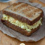 Egg Salad Sandwich on a brown piece of paper with a glass of water and white bowl of salad on a wooden surface (vertical with title overlay)