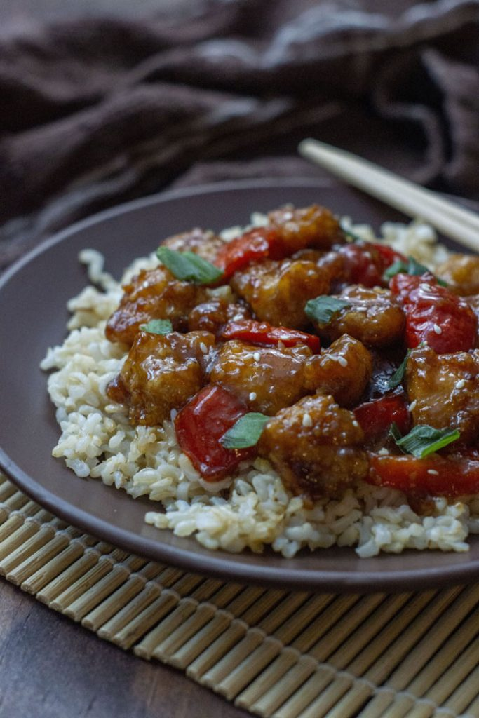 Quick & Easy General Tso's Chicken on a bed of rice on a round brown plate with bamboo chop sticks on top of a bamboo mat with a brown towel behind all on a wooden surface (vertical)