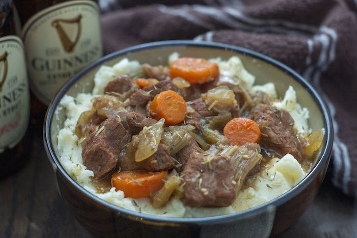Guinness Beef Stew over a bed of mashed potatoes in a brown bowl with a bottle of Guinness beer and a brown and white towel behind all on a wooden surface