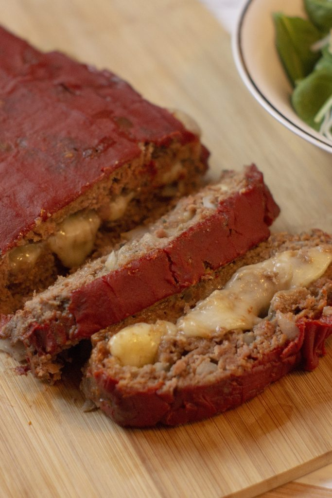 Mozzarella-Stuffed Meatloaf with a few slices laying on their side next to a bowl of salad on a bamboo surface (vertical)