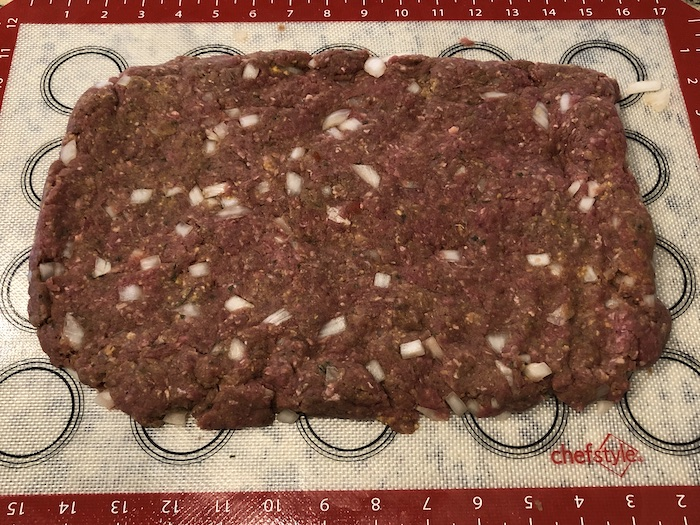 Meatloaf mixture spread out on a silicone baking mat