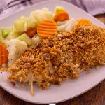 Parmesan crusted chicken next to steamed mixed vegetables on a white square plate with a white and brown towel behind all on a wooden surface (vertical with title overlay)