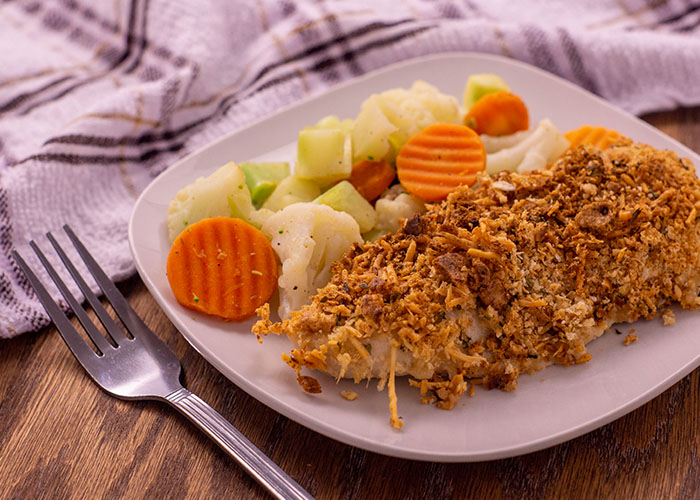 Parmesan crusted chicken next to steamed mixed vegetables on a white square plate with a white and brown towel behind and a stainless steel fork to the left side all on a wooden surface
