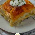 Square cut of pierogi lasagna topped with sour cream and seasonings on a round white plate on a white and grey towel all on a wooden surface (vertical with title overlay)