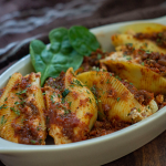 Cooked stuffed shells garnished with spinach in a white dish on a wooden surface