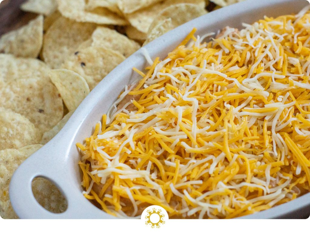Taco Dip covered with shredded blended cheese in an off-white serving dish with round tortilla chips behind the dish all on a wooden surface (with logo overlay)