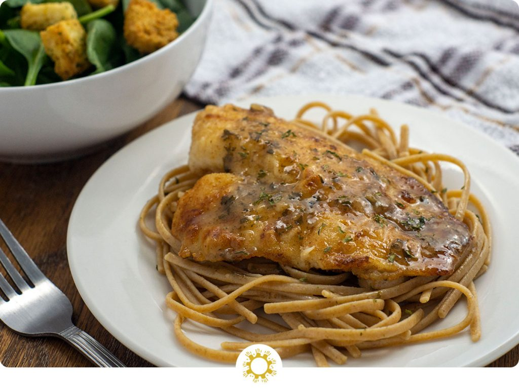 Tilapia with lemon butter sauce over a bed of spaghetti noodles on a round white plate next to a white bowl of salad and a stainless steel fork with a white and brown towel behind all on a wooden surface (with logo overlay)