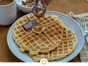 Two waffles with a pat of butter on a white plate with syrup pouring onto them next to a tan napkin with a fork and a cup of coffee and a yogurt parfait in the background on a wooden surface (with logo overlay)