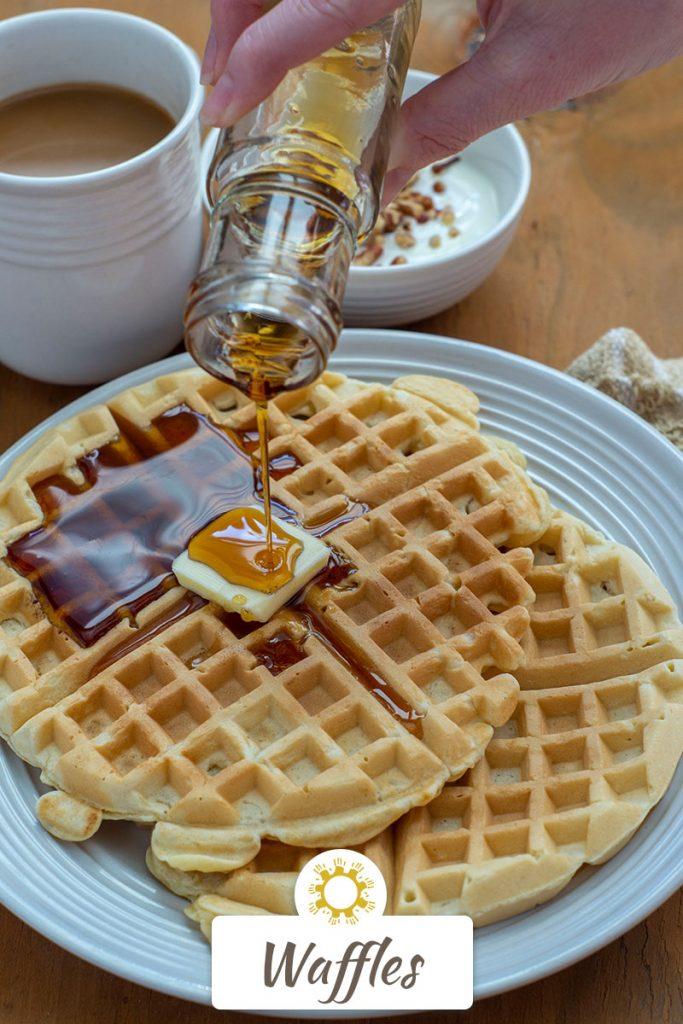 Two waffles with a pat of butter on a white plate with syrup pouring onto them next to a tan napkin with a fork and a cup of coffee and a yogurt parfait in the background on a wooden surface (with title overlay)
