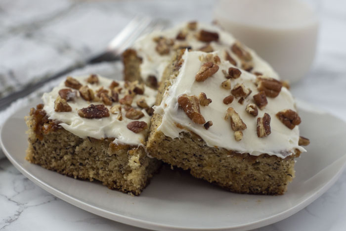 Three Banana Bread Bars topped with pecans on a square white plate with a stainless steel fork, glass of milk, and a white and grey towel behind the plate all on a white and grey marble surface