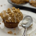 Banana Muffin drizzled with icing next to a spoon of icing and streusel crumbles on a round white plate with a glass of milk and the muffin pan behind all on a white surface