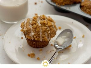 Banana Muffin drizzled with icing next to a spoon of icing and streusel crumbles on a round white plate with a glass of milk and the muffin pan behind all on a white surface (with logo overlay)