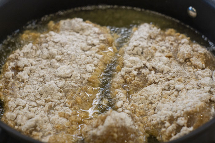 Uncooked breaded chicken starting to fry in oil in a large skillet