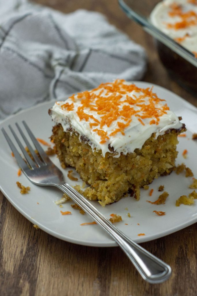 A slice of Carrot Cake with Pineapple Filling and cream cheese frosting on a white plate with a metal fork next to a white towel and the pan of cake in the background on a wooden surface (vertical)