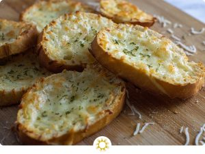 Cheesy Garlic Bread in a pile on a bamboo board (with logo overlay)