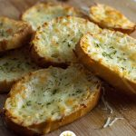 Cheesy Garlic Bread in a pile on a bamboo board (vertical with title overlay)