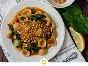 Chickpea and Spinach Orecchiette pasta on a round white dish next to a fork on a white and grey towel with a bowl of breadcrumbs in the background next to spinach leaves and a slice of lemon (with logo overlay)