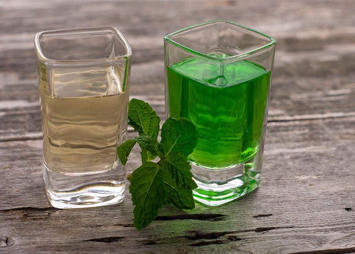 Two square glass shot glasses with clear creme de menthe in one and green creme de menthe in the other with a sprig of mint between on a wooden surface