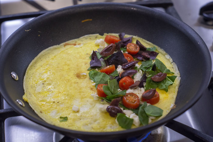 Cooked eggs in a skillet with greek omelet toppings on one half