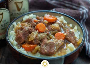 Guinness Beef Stew over a bed of mashed potatoes in a brown bowl with a bottle of Guinness beer and a brown and white towel behind all on a wooden surface (with logo overlay)
