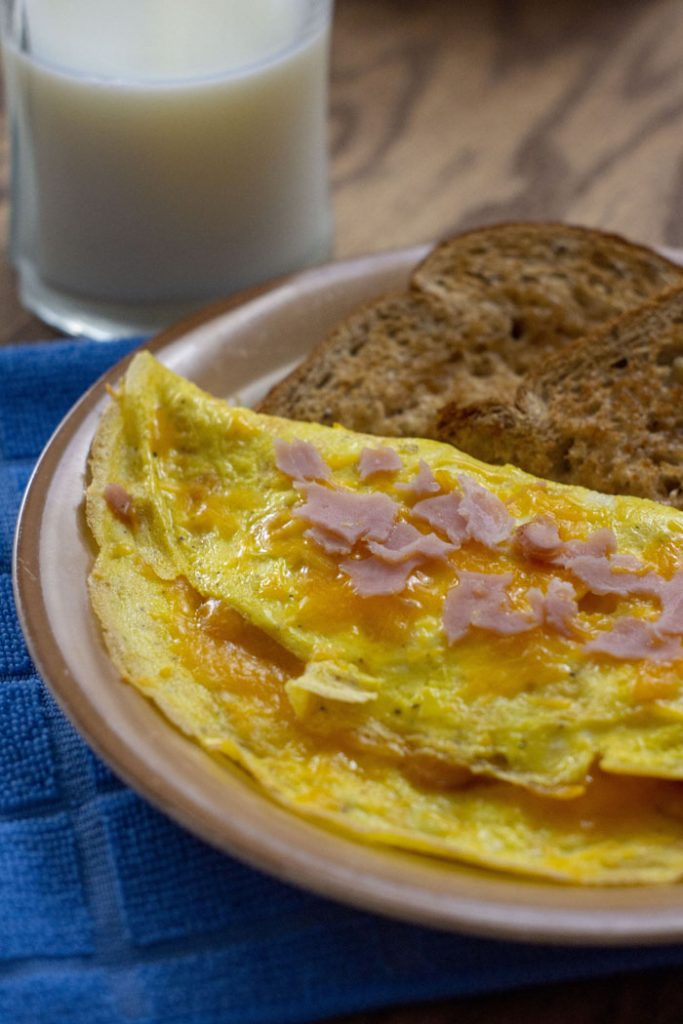 Ham and Cheese Omelet on a tan plate with toast next to a glass of milk and a blue towel on a wooden surface (vertical)