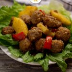Hawaiian meatballs with pineapple chunks and chopped red peppers on a bed of lettuce on a round white plate with a white and brown towel behind all on a wooden surface (vertical with title overlay)