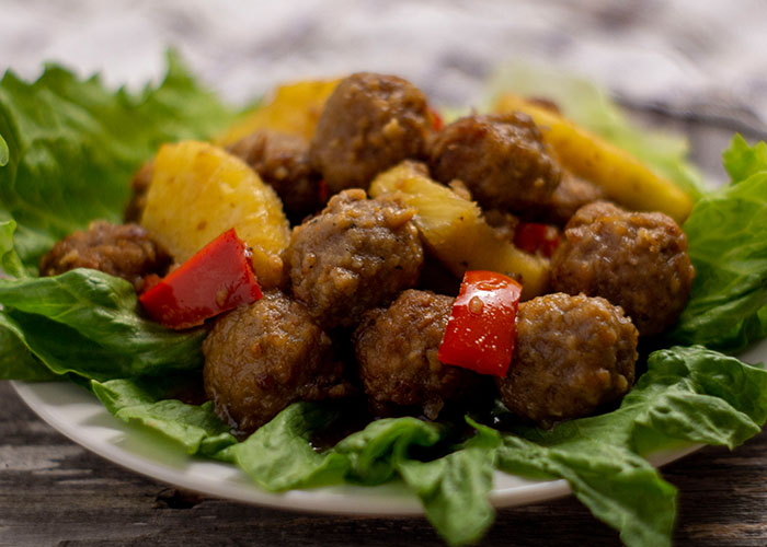 Hawaiian meatballs with pineapple chunks and chopped red peppers on a bed of lettuce on a round white plate with a white and brown towel behind all on a wooden surface