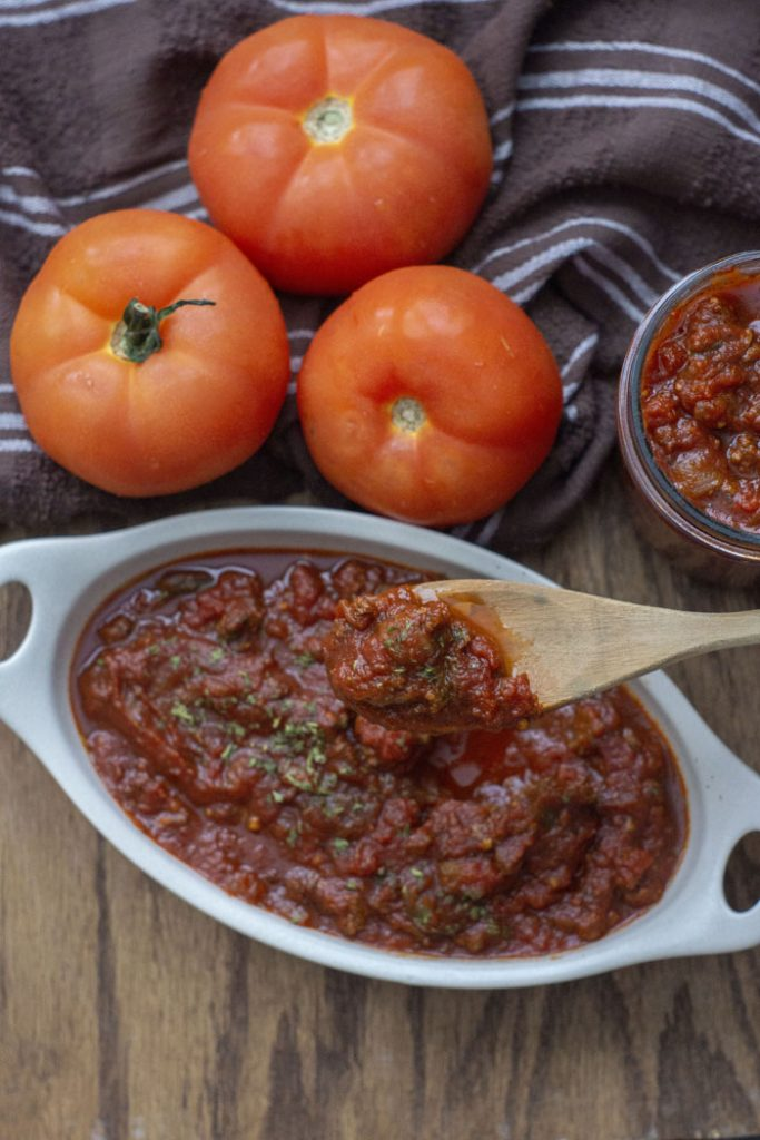 Meaty Marinara Sauce in a shallow white serving dish with a wooden spoon lifting a scoop next to three tomatoes on a brown towel and a jar of more sauce to the side all on a wooden surface (vertical)