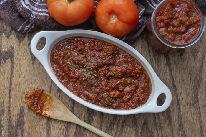 Meaty Marinara Sauce in a shallow white serving dish with a wooden spoon covered in sauce laying in front of it and to three tomatoes on a brown towel and a jar of more sauce to the side behind the dish all on a wooden surface
