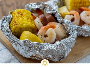 Shrimp boil foil wrap on a bamboo platter on a white and blue towel on a wooden surface (with logo overlay)