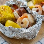 Shrimp boil foil wrap on a bamboo platter on a white and blue towel on a wooden surface (vertical with title overlay)
