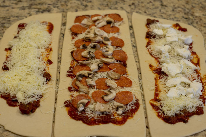 Stromboli dough rolled out on a granite surface covered with sauce, cheese, and other toppings