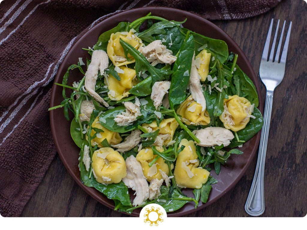 Chicken Tortellini Salad with Lemon Dressing on a round brown plate next to a fork on a wooden surface (with logo overlay)