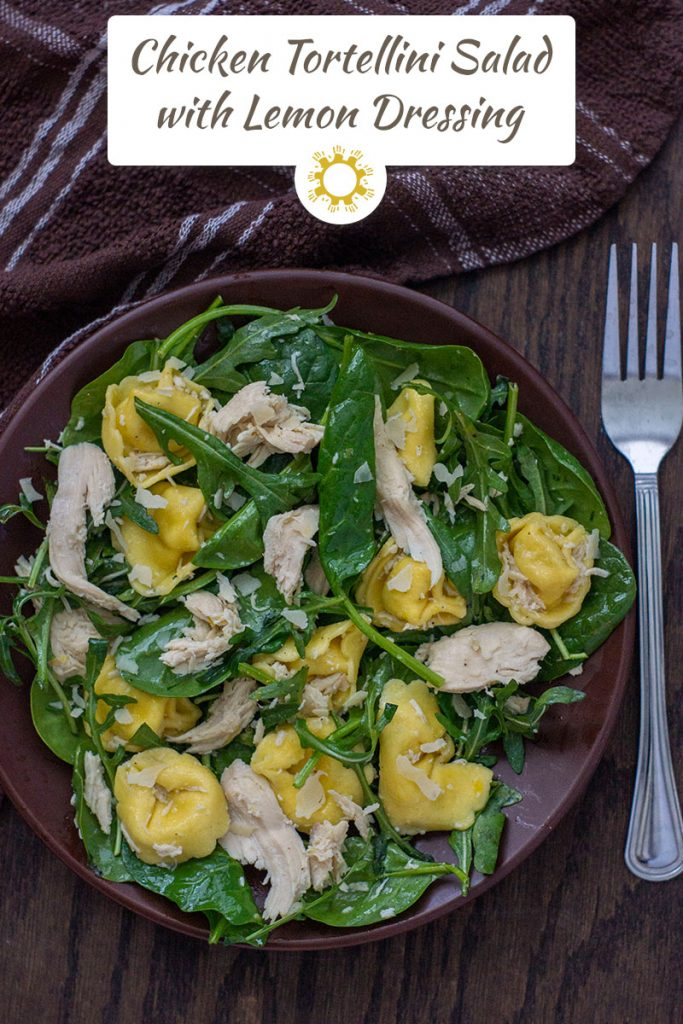 Chicken Tortellini Salad with Lemon Dressing on a round brown plate next to a fork on a wooden surface (with title overlay)