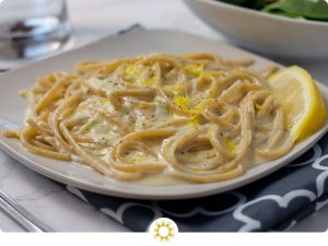 Creamy Lemon Pasta on a square white plate with a salad and glass of water in the background (with logo overlay)