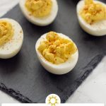 Classic deviled eggs on a slate tray on top of a white and grey marble surface (vertical with title and description overlay)
