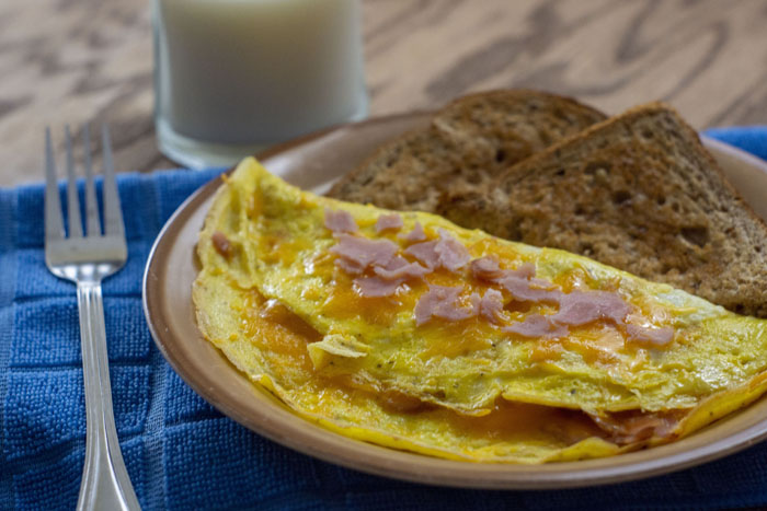 Ham and Cheese Omelet on a tan plate with toast next to a glass of milk and a blue towel on a wooden surface