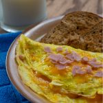 Ham and Cheese Omelet on a tan plate with toast next to a glass of milk and a blue towel on a wooden surface (vertical with title overlay)
