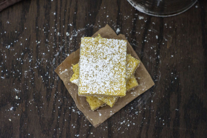Top-down view of three lemon bars stacked on top of each other sprinkled with powdered sugar sitting on a piece of brown paper on a wooden surface