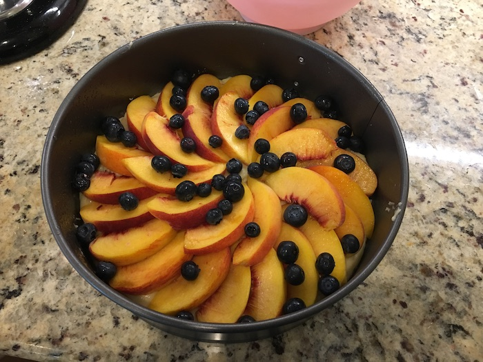 Peach and Blueberry cake in a springform pan ready to be baked sitting on a granite surface