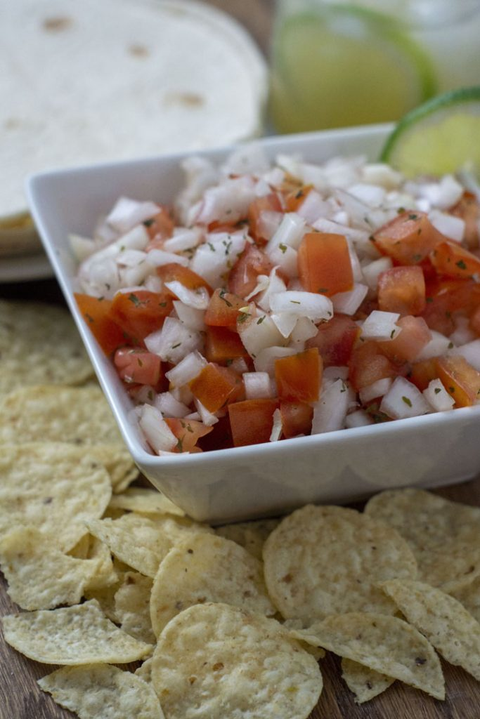 Pico de Gallo in a square bowl with chips in front of the bowl and tortillas behind it all on a wooden surface (vertical)