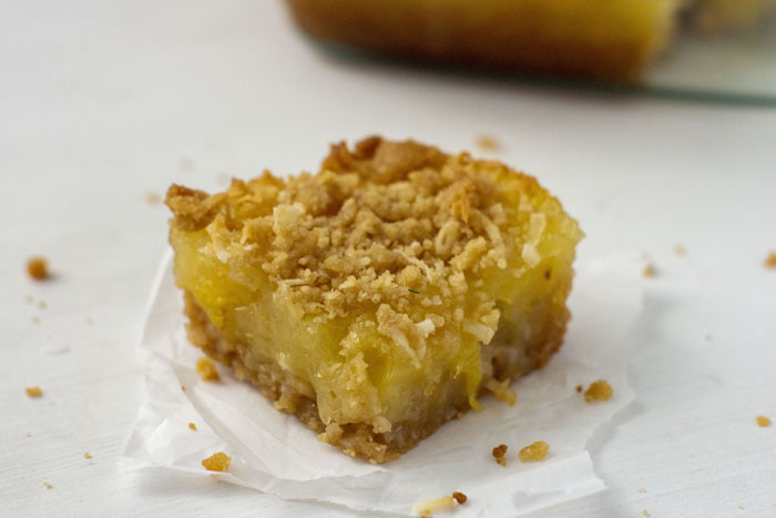 One Pineapple Coconut Dessert Bar on a piece of parchment paper on a white surface with the glass dish of bars in the background