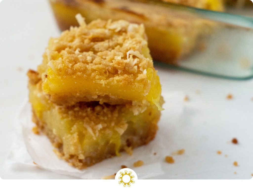 Two Pineapple Coconut Dessert Bars on a piece of parchment paper on a white surface with the glass dish of bars in the background (with logo overlay)
